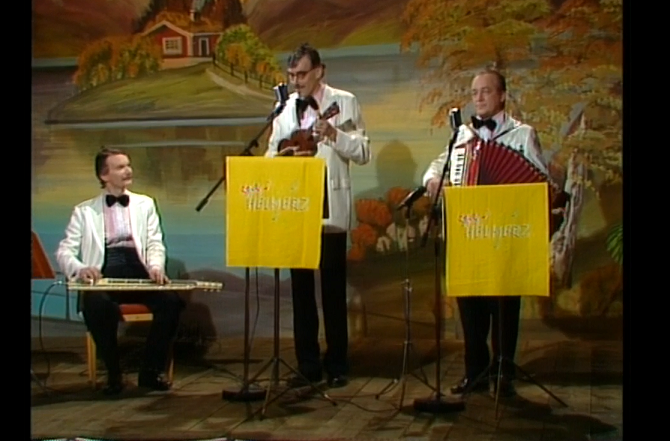 Trio med lapsteel, ukulele och dragspel på en folkparksscen.