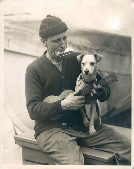 Man med stickad mössa spelar ukulele och munspel med en hund i knät. I bakgrunden en livbåt.