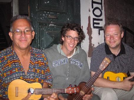 Tre män med ukuleler på en farstutrapp.
